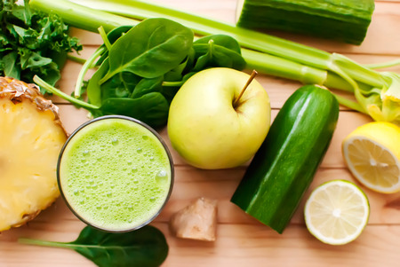and pineapple juice: healthy organic green detox juice on wood