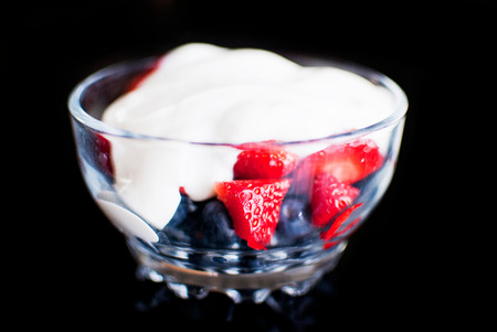 srawberries: strawberry and blueberry yogurt in a bow isolated on black