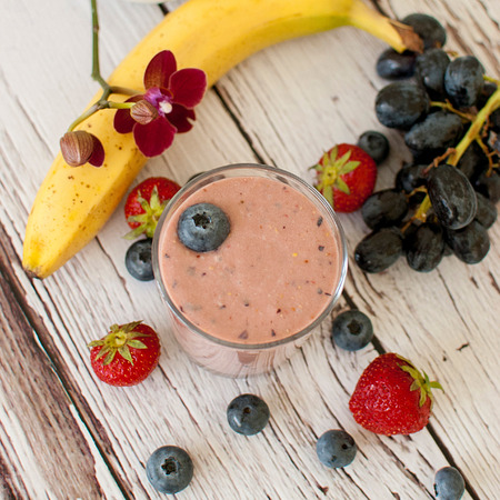 kefir: healthy organic fruit and nuts smoothie on wooden board