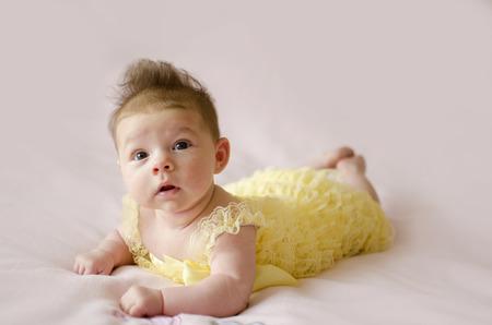 tummy: beautiful baby girl lying on tummy wearing yellow dress