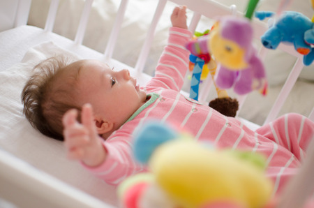 cot: little cute baby girl playing in a cot