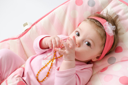 teething: beautiful baby girl chewing amber teething necklace