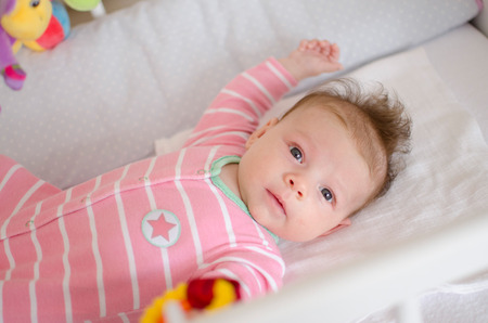 baby playing toy: little cute baby girl playing in a cot