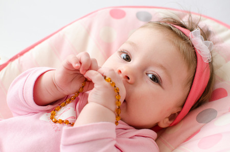 beautiful baby girl chewing amber teething necklace