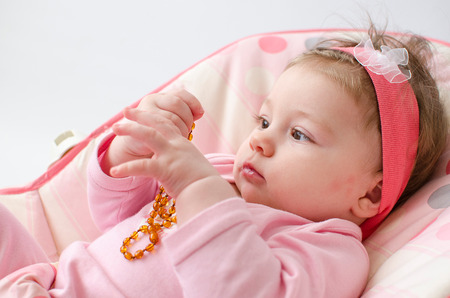 teether: beautiful baby girl chewing amber teething necklace