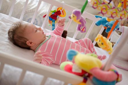 kleine süße Baby in einem Kinderbett spielen Standard-Bild