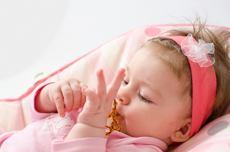 teething: beautiful baby girl chewing amber teething necklace