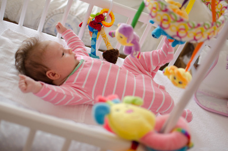 1 2 month: little cute baby girl playing in a cot