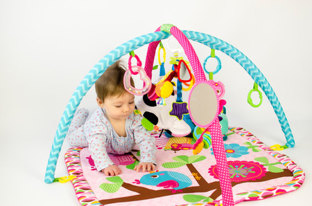 baby playing: cute baby girld playing in an activity gym
