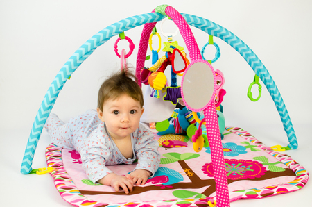 playmat: cute baby girld playing in an activity gym
