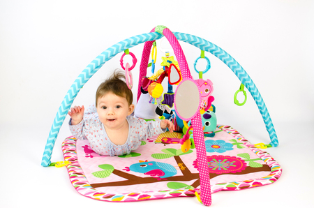 developmental: cute baby girld playing in an activity gym