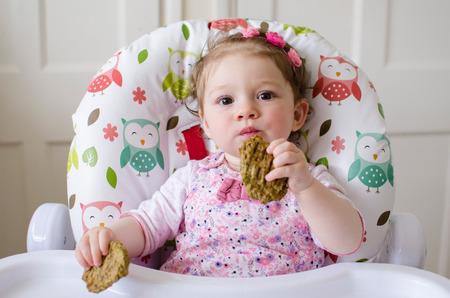 bebé niña llevó el destete comer albóndigas de pollo a la parrilla para el almuerzo