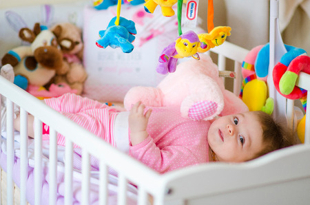 little cute baby girl playing in a cot