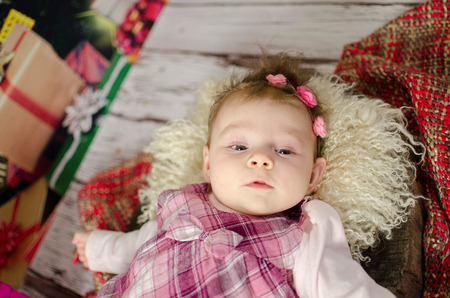 baby girl enjoying her first Christmas with lots of gifts under Christmas tree Stok Fotoğraf