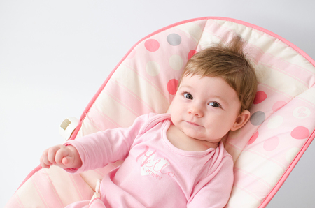 beautiful happy baby girl in a bouncer wearing pink Stock Photo
