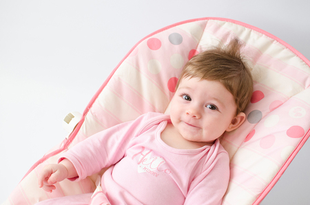 HI: beautiful happy baby girl in a bouncer wearing pink Stock Photo