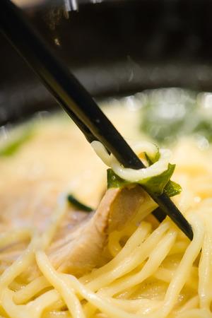 Delicioso menú de estilo de comida japonesa.Fideos ramen locales japoneses tradicionales en plato negro.Chicero japonés cocinando fideos ramen en el restaurante japonés.La deliciosa comida japonesa servida en un plato.
