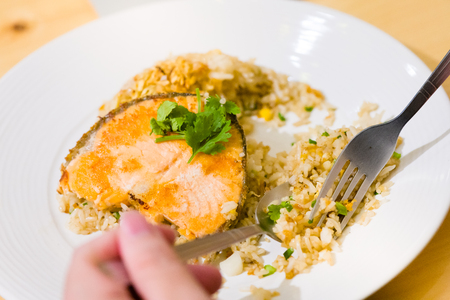fried sliced salmon with fried rice.man hands use fork and spoon for fusion food.sliced salmon with rice on white plate in restaurant or cafe.man sitting and eating sliced salmon on laptop background