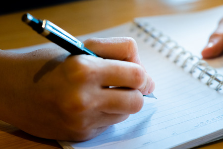 female hand with pencil writing on notebook at coffee shop.woman working by hand writing on letter paper on the wooden desk.woman hand writing. Stock fotó