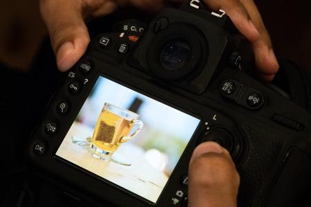 professional photographer take photo and check image tea bag photo on back  camera monitor.scan and check photo behind camera monitor view image