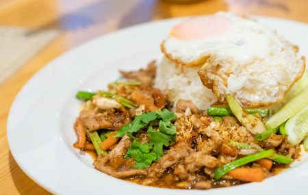 delicious Thai food garlic and pepper with pork and Fried egg with jasmin rice closeup with carrot cucumber Spring onion and coriander leaves on top in white plate on wooden background.  delicious Thai food at Thailand in daylight.
