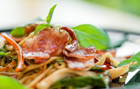 delicious spicy spaghetti dried chilli and basil sauce with bacon and mushroom ,beautiful close up spicy spaghetti bacon on black plate with some space for text. Stock fotó