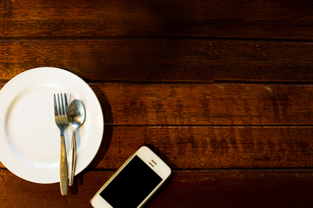 An empty white dinner dish with set on a rustic wooden table top background.