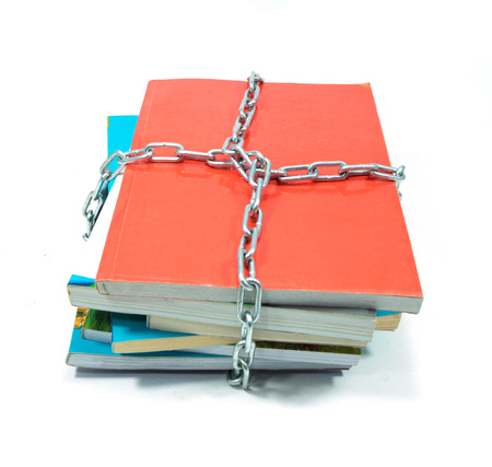 pile of books with a chain isolated on white