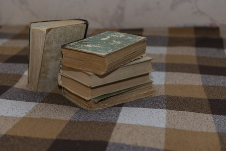 bookseller: stack of battered old books on a plaid