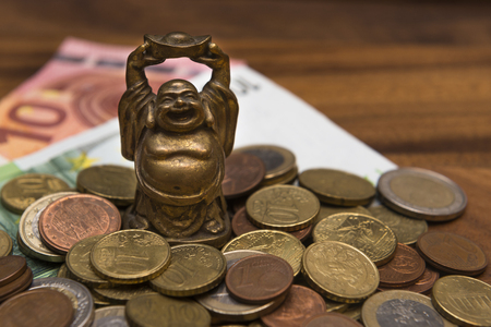 talismán: Talisman netske Hotei coins Euro banknotes on a wooden table Foto de archivo