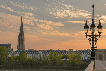 Pont de Pierre stone bridge on the river garonne in Bordeaux, France at sunset with the st michel church in the background