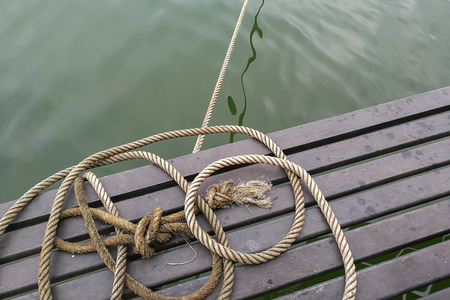 ship bow: boat rope , rope knot on wood and water Stock Photo