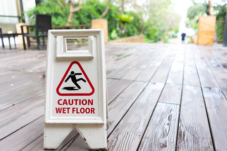 Caution wet floor sign with wooden background