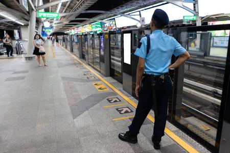 BTS skytrain guard standing at platform in Bangkok, Thailand.