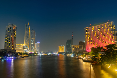 Cityscape riverfront with long exposure light on the bridge. Bangkok, Thailand. night scene.