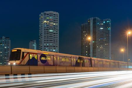 BTS sky train with long exposure light on Taksin Bridge, Bangkok, Thailand. cityscape background.