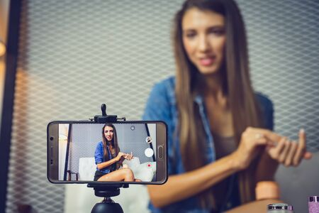 Young beauty blogger selling her cosmetic on live stream broadcasting by mobile phone.