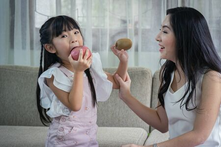 Happy together! Asian mother and her daughter funny together with their fruits at sofa. single mom concept.