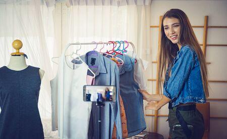 Chica joven que vende ropa en línea por transmisión en vivo desde el teléfono móvil.