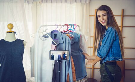 Young girl selling clothes online by live streaming from mobile phone. Reklamní fotografie