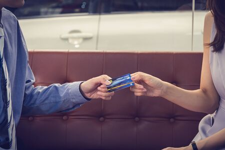 Attractive Asian girl millenials buying a new car with credit card. Film effected. Close-up scene