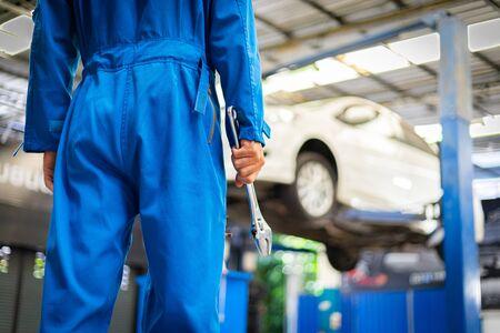 Mécanique tenant une clé dans le garage de l'atelier. Concepts de services automobiles