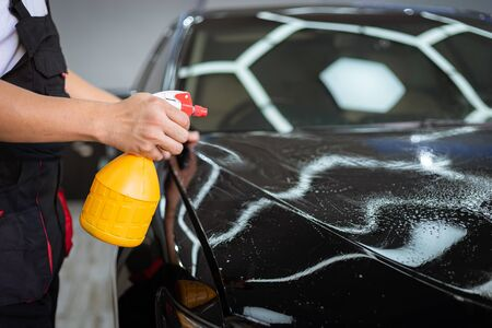 Car cleaning auto service : the man sprays water - car detailing concepts