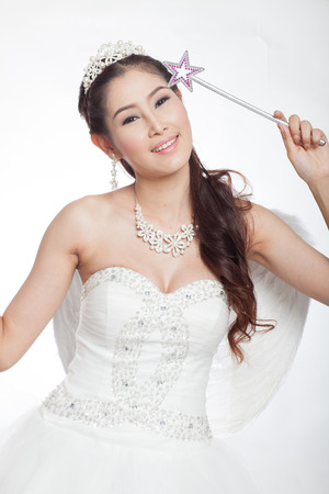 scettro: ritratto di bella donna asiatica in abito da sposa bianco con scettro fata con ali d'angelo, sorridente in studio luce, sfondo bianco