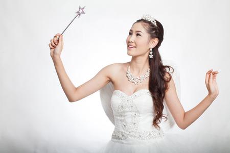 cetro: bello retrato de mujer asi�tica en vestido de novia blanco con cetro de hadas con alas de �ngel, sonriendo a la luz del estudio, fondo blanco Foto de archivo