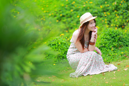 sitting on the ground: Asian beautiful young girl,wear florals maxi dress and hat, sitting on the ground at spring
