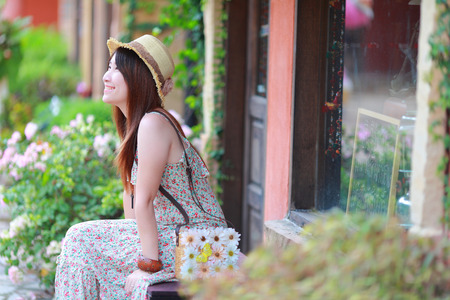 maxi: Asian beautiful young girl,wear florals maxi dress and hat, sitting on the bench at spring