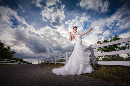 sweet grasses: portrait asian beautiful bride in forest,blue sky in twilight