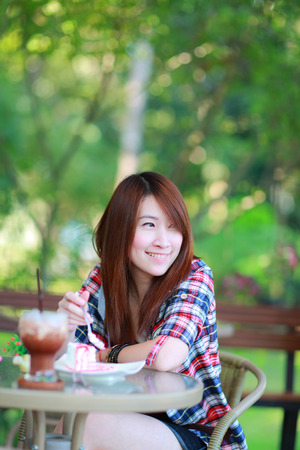 20 years old: closeup portrait of the asian girl 20 years old posing outdoors wear plaid shirt,sitting and eating cake and afternoon tea,pgarden view in the afternoon in warm color tone