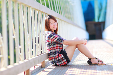 20 years old: portrait of the asian girl 20 years old posing outdoors wear plaid shirt,sitting on white bridge ,park view in the afternoon in warm color tone Stock Photo